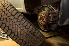 Mechanician zmieniać samochodowy toczy wewnątrz garaż Mężczyzna wymienia oponę Opony us?uga zdjęcie royalty free