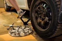 Mechanician zmieniać samochodowy toczy wewnątrz garaż Mężczyzna wymienia oponę Opony us?uga obrazy stock
