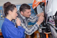 Mechanicians fixing motocycle at garage. Mechanicians fixing motocycle at the garage Royalty Free Stock Photo
