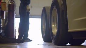 Mechanick в гараже около дверей гаража тележки заключительных на предпосылке видеоматериал