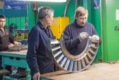 Mechanics assembles turbine for aviation engine Royalty Free Stock Photo