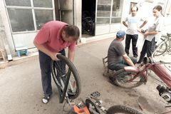 Mechanics Of Bicycles And Old Scooters In Pirot, Serbia. PIROT, SERBIA - JULY 27, 2017: mechanics that repairs bicycles and old scooters is working on the royalty free stock photo