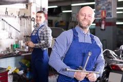 Mechanics in a bike repair station Stock Images