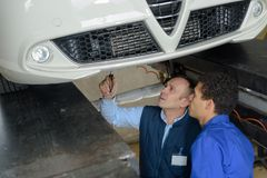 Mechanics checking technical state underneath car. Mechanics checking the technical state underneath a car Royalty Free Stock Image