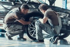 Mechanics Checking Wheel Bearings in Car Workshop. Two Professional Caucasian Adult Technician Master in Uniform in Front of Automobile in Garage. Repairing royalty free stock photos