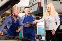 Mechanics and client at car dealership Stock Photo