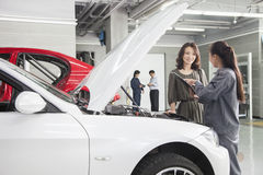 Mechanics and Customers in Auto Repair Shop Stock Images