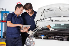 Mechanics Discussing While Using Tablet Computer By Car Royalty Free Stock Image
