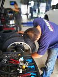 Mechanics are doing the work. Some mechanics are doing the work of converting the michelin pilot sport tires to honda civic cars in car workshops and tyre Stock Photo
