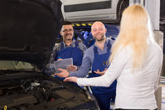 Mechanics explain car problem to owner. Two mechanics at a car repair shop explain the problem with anautomobile to an owner Royalty Free Stock Image