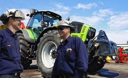 Mechanics, farmers with tractor and plow. Two mechanics with tractors and plows, latest models Stock Photo