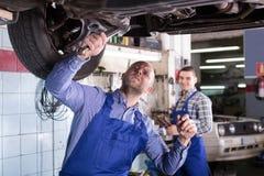 Mechanics fixing car. Happy mechanics fixing car tire leak Stock Image