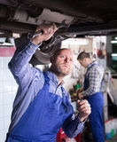 Mechanics fixing car. Positive european  mechanics fixing car tire leak Stock Images