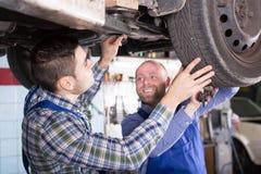 Mechanics fixing car. Positive  professional mechanics fixing car tire leak Royalty Free Stock Photos