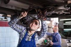 Mechanics fixing car. Positive mechanics fixing car at workshop Stock Photos