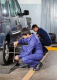 Mechanics Fixing Car Tires At Garage Stock Images