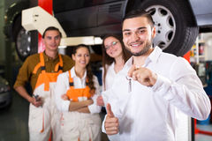 Mechanics and happy customer. Portrait two cheerful troubleshooters showing fixed car to satisfied client Royalty Free Stock Photography