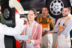Mechanics and happy customer. Two smiling troubleshooters showing fixed car to cheerful client Royalty Free Stock Photo