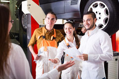 Mechanics and happy customer. Two troubleshooters and manager showing fixed car to cheerful client Royalty Free Stock Photography