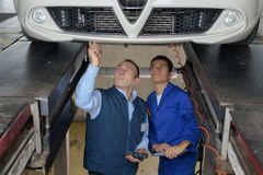 Mechanics inspecting lifted car. Mechanics inspecting a lifted car Royalty Free Stock Photo