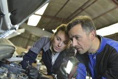 Mechanics instructor teaching apprentice. Mechanics instructor teaching women in apprenticeship Stock Photos