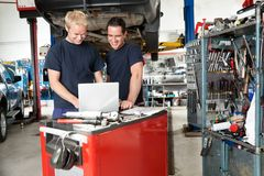 Mechanics with laptop in garage Royalty Free Stock Image