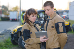 Mechanics looking at computer tablet in front parked quads Royalty Free Stock Photos