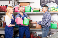 Mechanics offering antifreeze to customer. Mechanics offering their client different types of antifreeze liquid: pink and green Royalty Free Stock Image