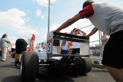 Mechanics pushing Formula Russia car Royalty Free Stock Image