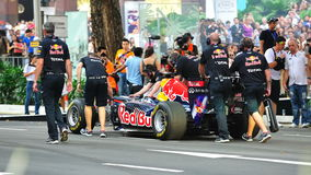 Mechanics pushing Red Bull Racing F1 car Royalty Free Stock Images