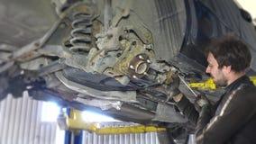 Mechanics removing worn broken car parts in garage under the automobile. Mechanics removing worn broken car parts with huge screwdriver in garage under the stock video