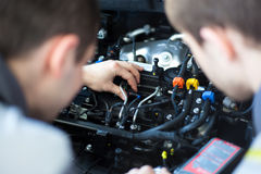 Mechanics at repair shop. two confident mechanics working on a car engine Stock Photography