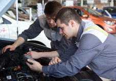 Mechanics at repair shop. two confident mechanics working on a car engine. Mechanics at repair shop. Top view of two confident mechanics working on a car engine Royalty Free Stock Photo