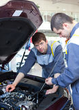 Mechanics at repair shop. two mechanics working on a car engine Stock Image