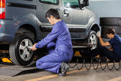 Mechanics Repairing Car Tires. Young male mechanics repairing car tires at garage Royalty Free Stock Photography