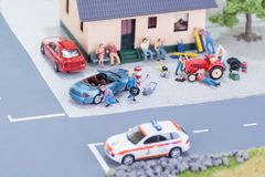 Mechanics repairing a car and a tractor. Miniature mechanics repairing a convertible car and a farm tractor close-up Stock Photos