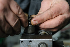 Mechanics repairing a diesel injector. Royalty Free Stock Photography