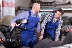 Mechanics repairing scooters Royalty Free Stock Photo