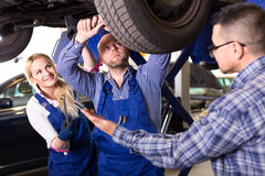 Mechanics repairing suspension. Driver has brought his car to a workshop. Mechanics a men and a women are repairing suspension on a lifted up car Royalty Free Stock Photos