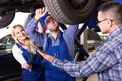 Mechanics repairing suspension Royalty Free Stock Photos