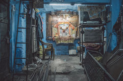 Mechanics shop. JODHPUR, INDIA - 17 FEBRUARY 2015: Empty mechanics shop with small shiva temple in background. Post-processed with grain and texture Royalty Free Stock Photos