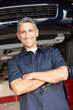 Mechanics standing in front of car Stock Images