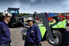 Mechanics, tractors and plows. Modern farmers, mechanics with giant tractor and plow, mower Royalty Free Stock Photography
