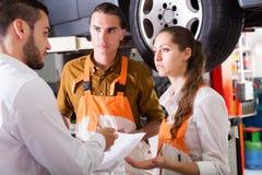 Mechanics trying to cheat client. Two mechanics trying to cheat serious client at workshop Stock Photos