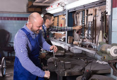 Mechanics at work in repair shop Royalty Free Stock Images