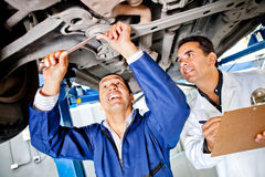 Mechanics working under a car Stock Photos