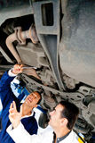 Mechanics working under a car Royalty Free Stock Photos