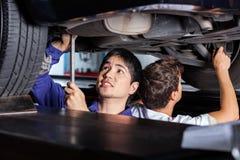 Mechanics Working Under Car Royalty Free Stock Photo