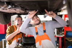 Mechanics working under a car Stock Images