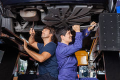 Mechanics Working Under Lifted Car Royalty Free Stock Image